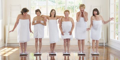 Older women weighing themselves in a row