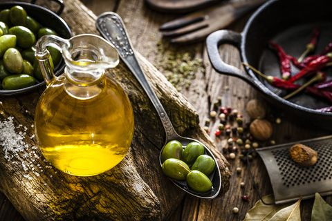 Olive oil bottle and green olives shot on rustic wooden table