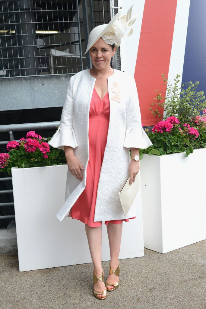 Olivia Colman adhered to the dress code at the Royal Ascot Races, wearing an elegant white coat over her pink tea-length dress. To top off the look, she also wore an elaborate white floral fascinator.