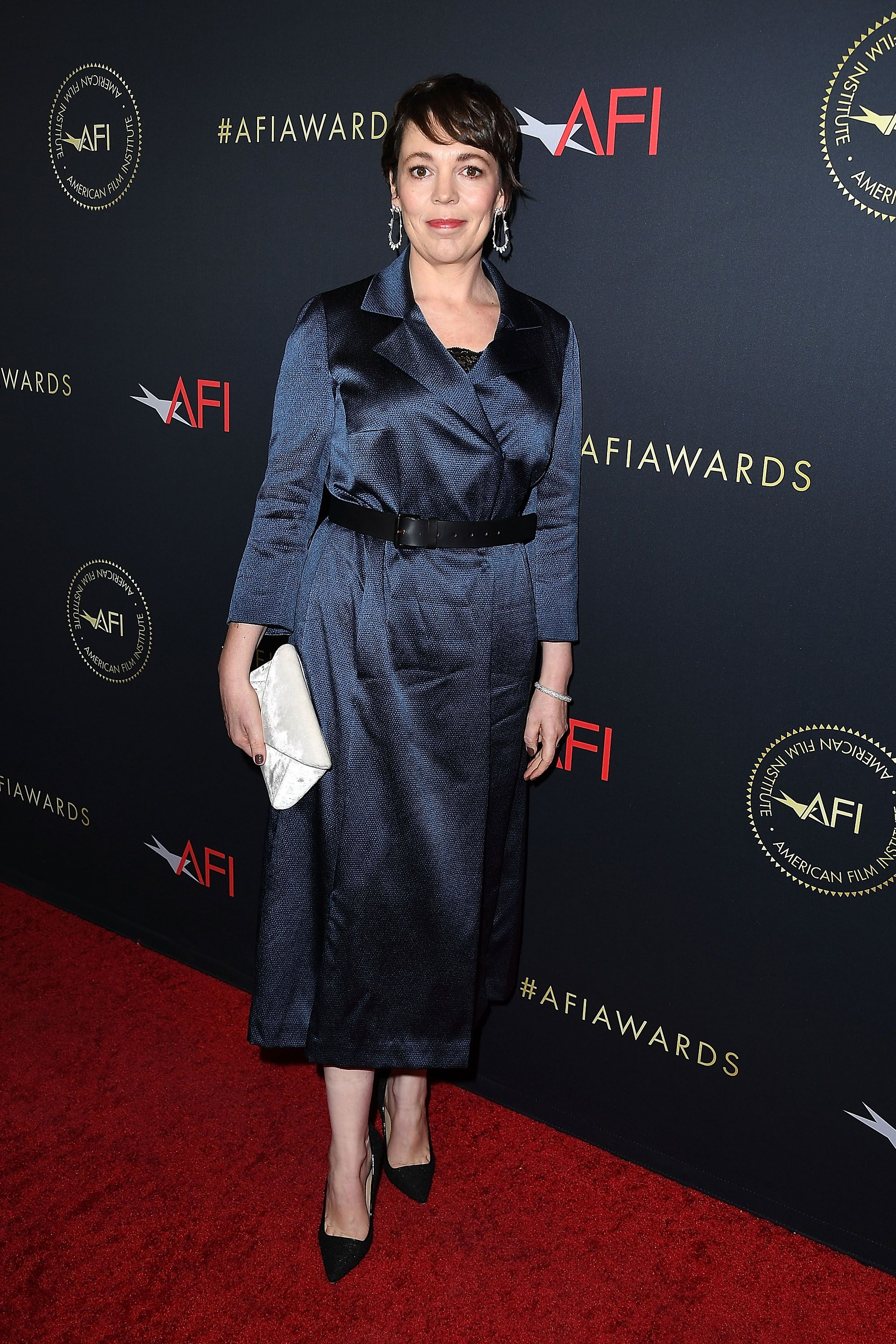 Olivia Colman attended the American Film Institute Awards wearing a navy silk dress with a black belt at her waist, hoop earrings, a white velvet clutch, and black stilettos.