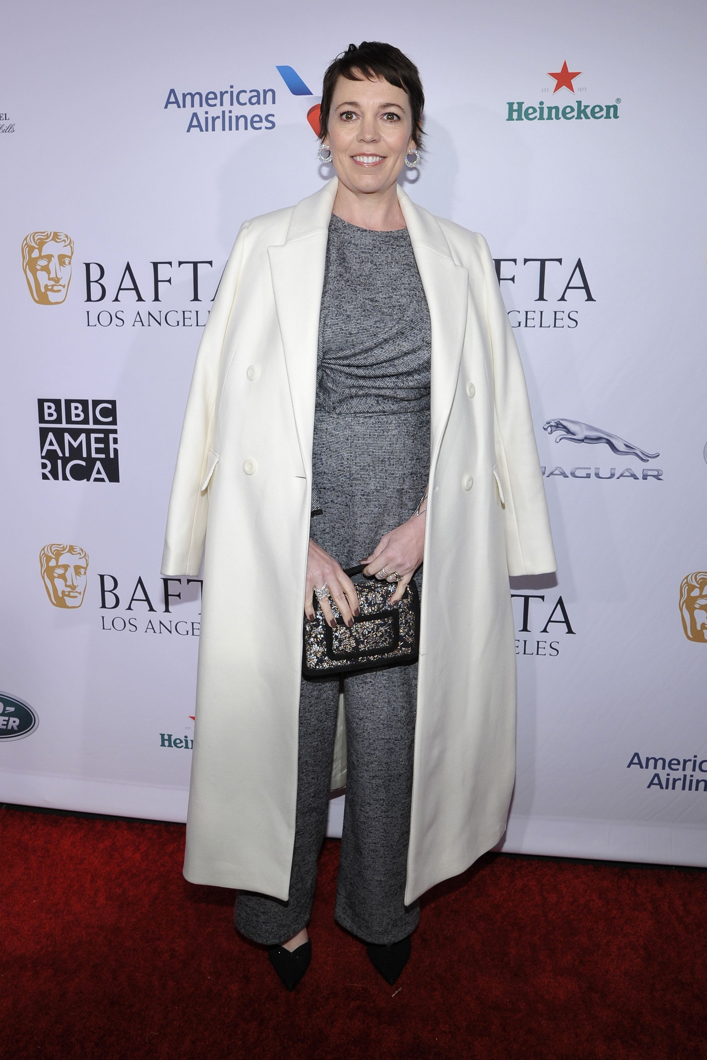 Colman wore an oversized white coat over a gray jumpsuit to the BAFTA Los Angeles Tea Party. The actress paired the look with an embroidered clutch and statement earrings.