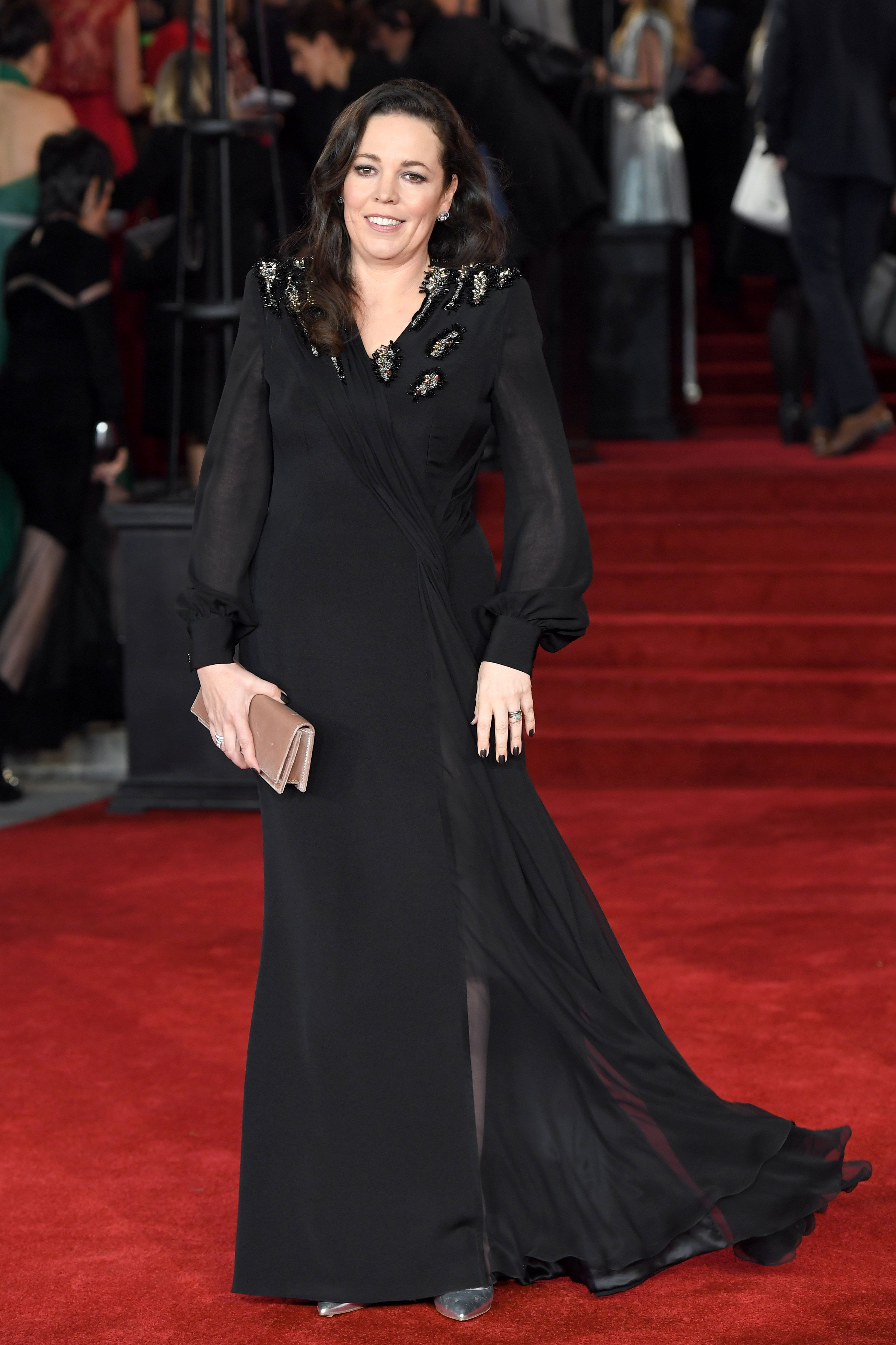 The actress looked elegant in a black wrap dress with sequin details for the premiere of Murder on the Orient Express at Royal Albert Hall. Olivia paired the flowing gown with a blush clutch and jewelry by DeBeers .