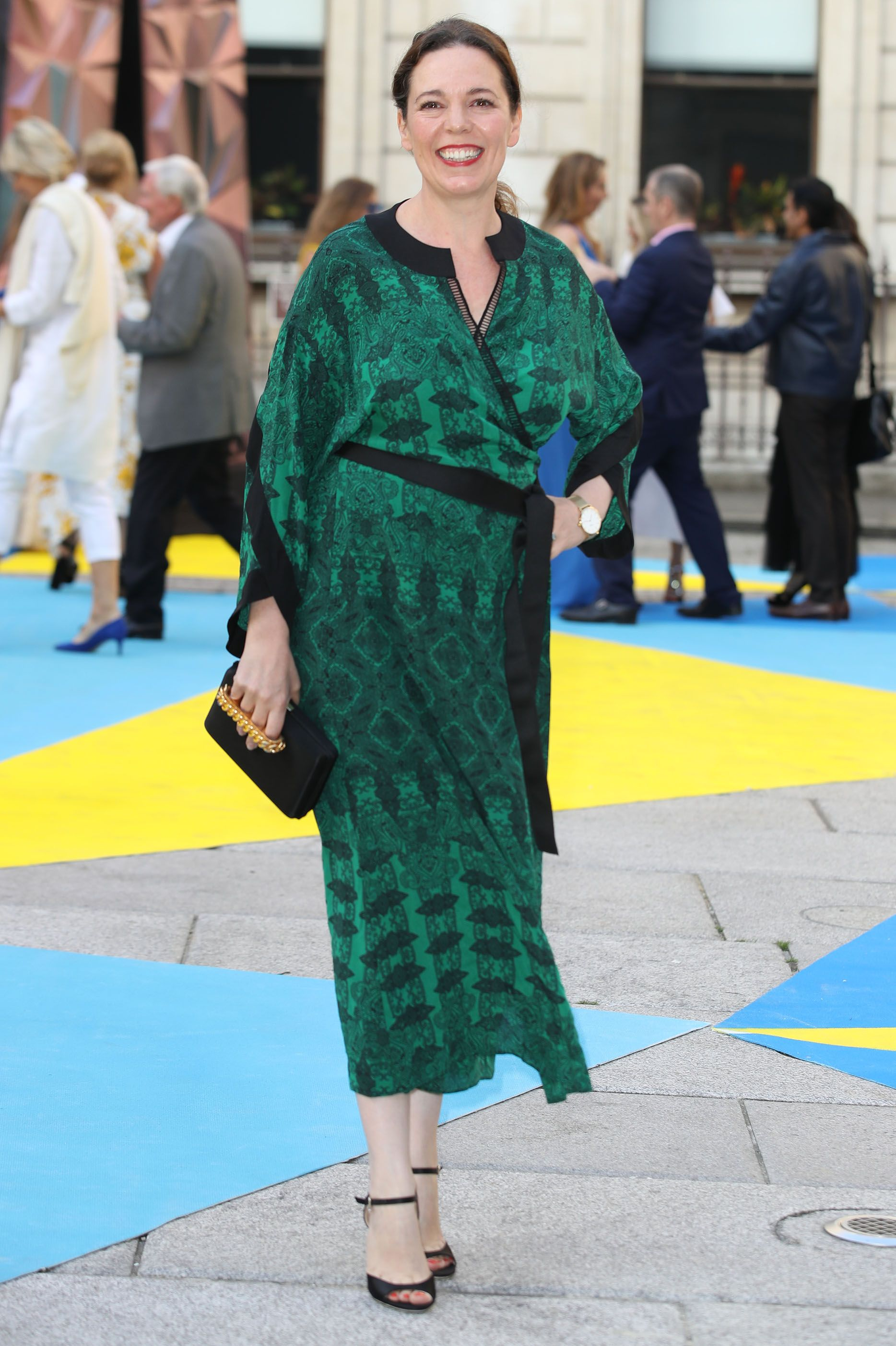 The actress paired a green printed wrap-dress with black heels and a black and gold-chained clutch for the Royal Academy of Arts Summer Exhibition Preview Party.