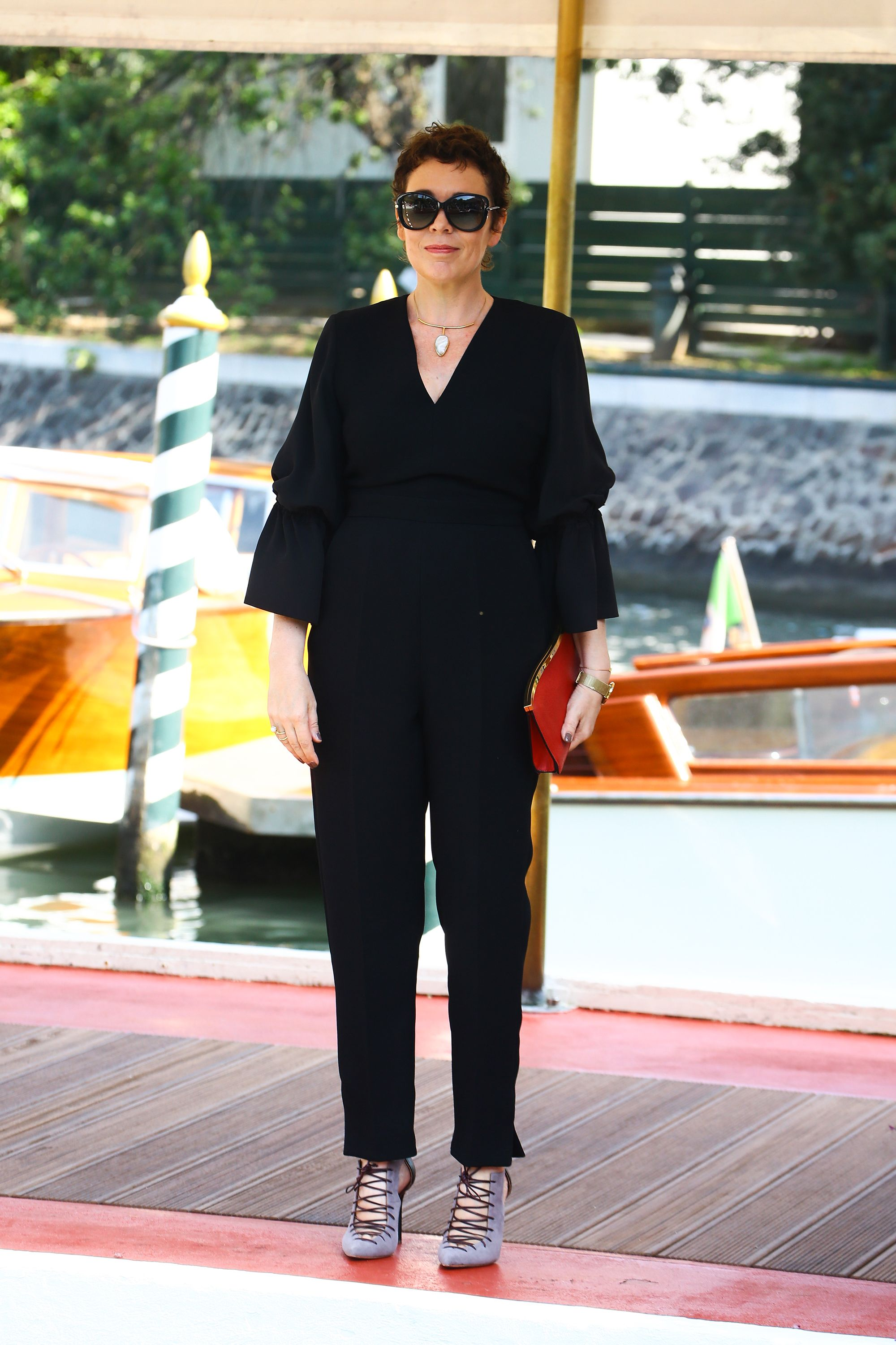 Arriving at the Venice Film Festival, Olivia Colman kept it casual in a classic black jumpsuit, gray lace up pumps, and a red clutch.