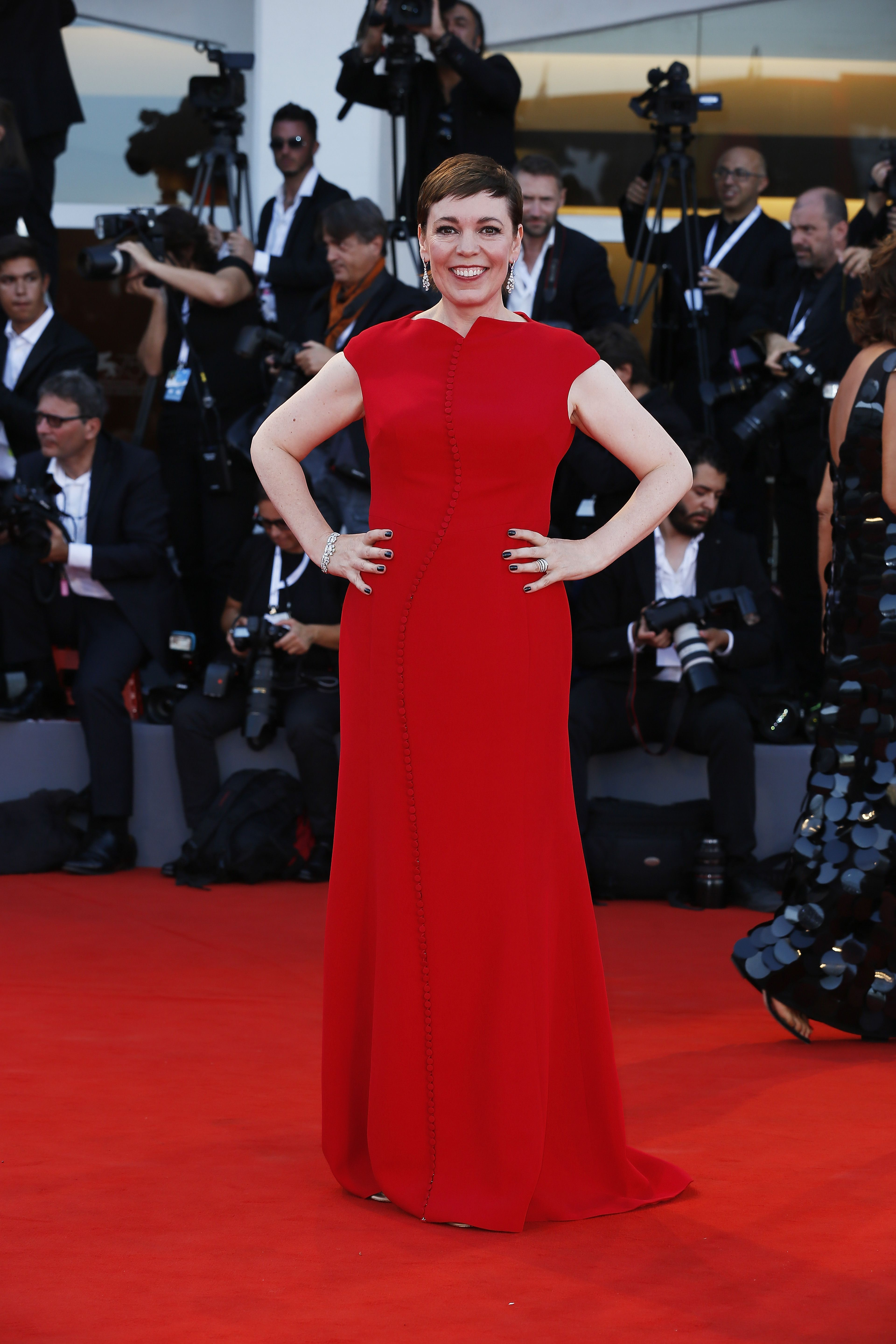 Olivia Colman stood out from the crowd in a bright red gown and diamond drop earrings on the red carpet at the Venice Film Festival.