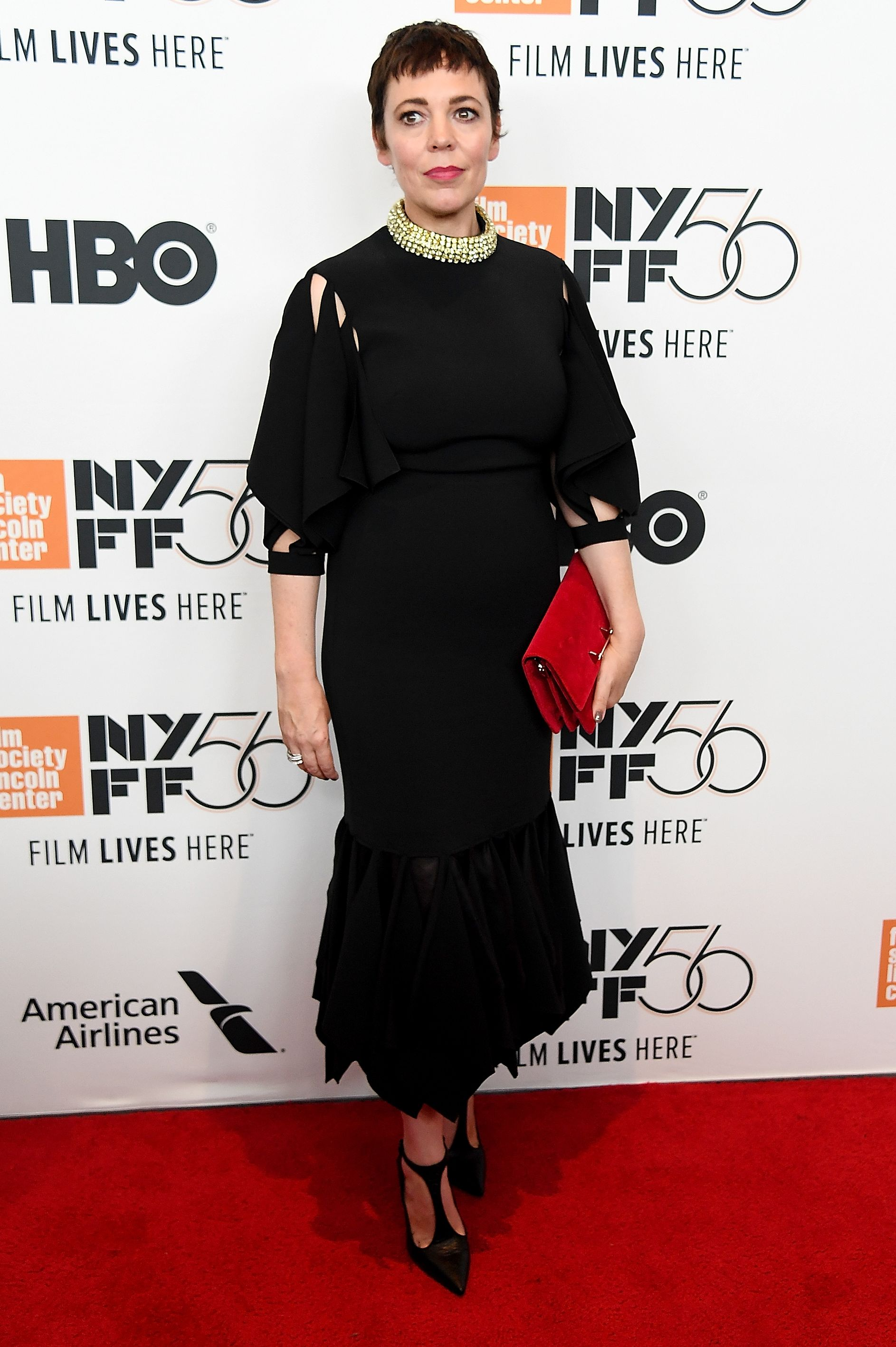 Actress Olivia Colman attended the New York Film Festival wearing a black dress with cut-out sleeves and a gold beaded collar, a red envelope clutch, and black pumps.