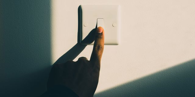 a woman's hand turning on a light switch