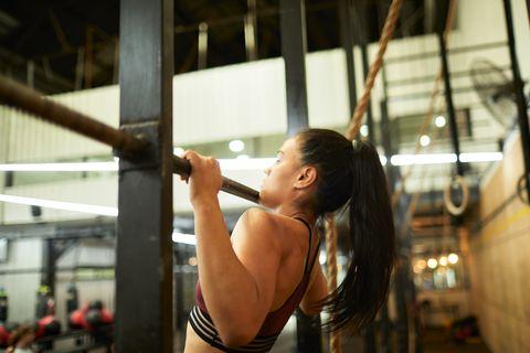 mujer haciendo dominadas en un gimnasio