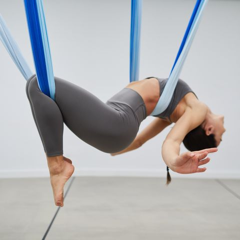 one fit woman practicing aerial yoga