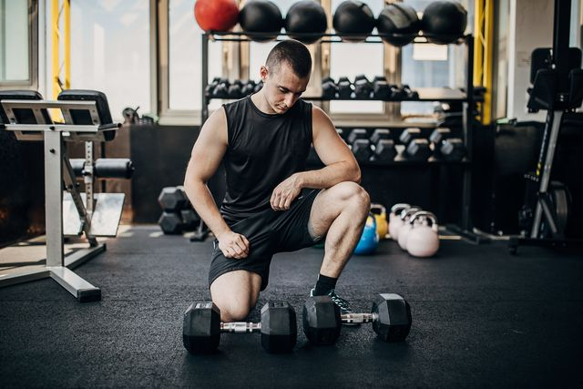 one male athlete training with dumbbells in the local gym