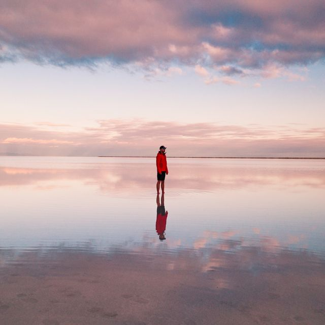 one person standing on the flooded bonneville salt flats, utah, united states of america