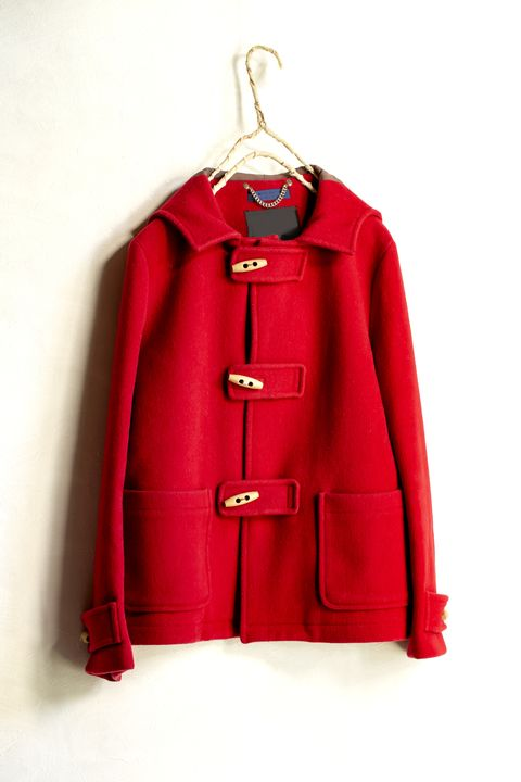 red wool short coat hanging on clothes hanger on white background