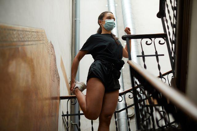mujer con mascarilla estirando en la escalera de su casa