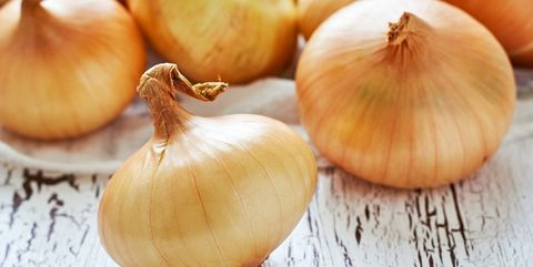 Onions on white rustic wooden background