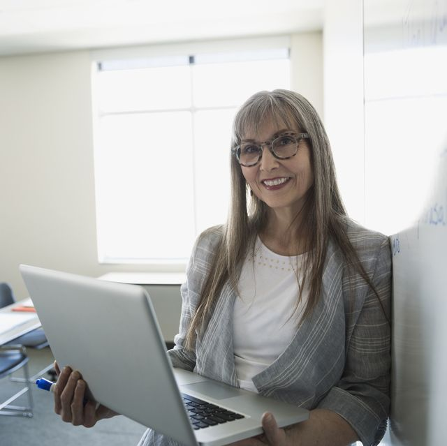 Portrait smiling professor with laptop at whiteboard in classroom