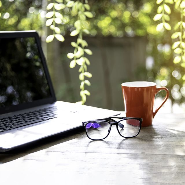 open laptop with glasses and red cup of tea on  wooden table