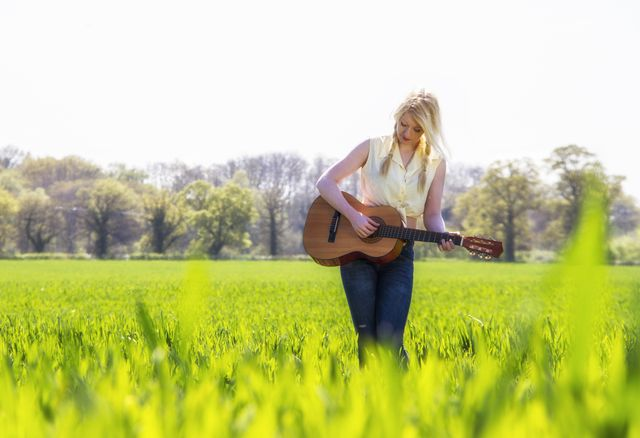 female country singer in grass field