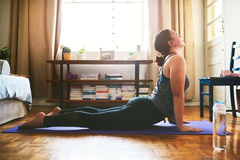 a woman stretching her abs on a yoga mat in cobra pose