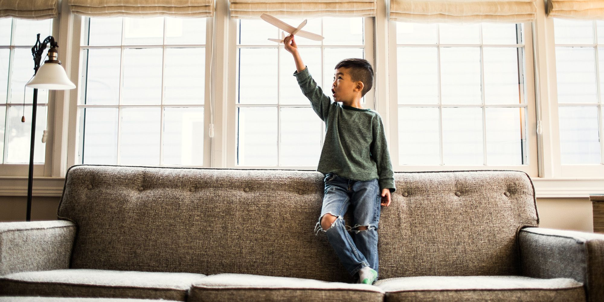Boy playing with toy glider at home