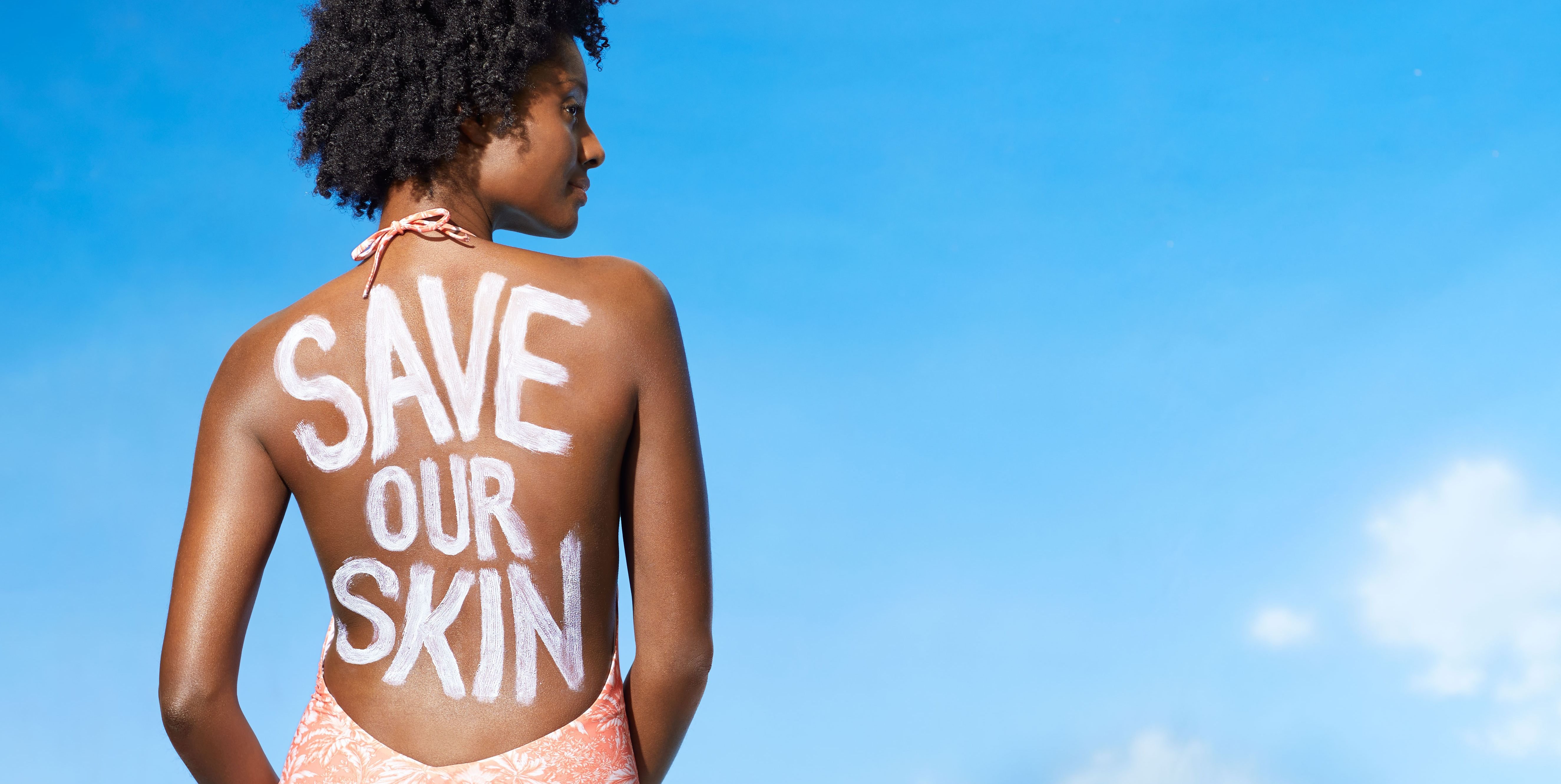 Black woman in bathing suit with sunscreen