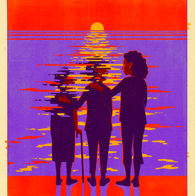 three women standing looking out at a sunset over water
