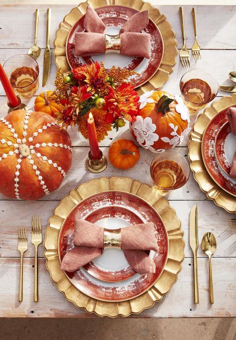 bowtie napkins on orange transferware plates with gold charger and flatware