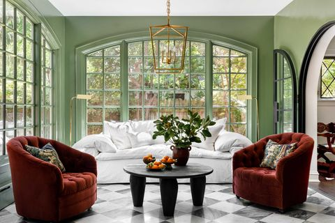 sitting room in screen porch, green walls, white couch, red lounge chairs