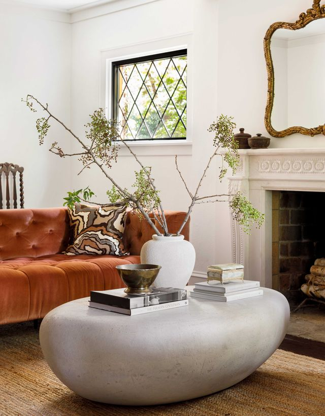 living room with orange sofa, fireplace and stone coffee table