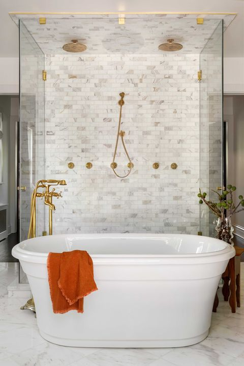 white bath tub with gold faucets and gold shower