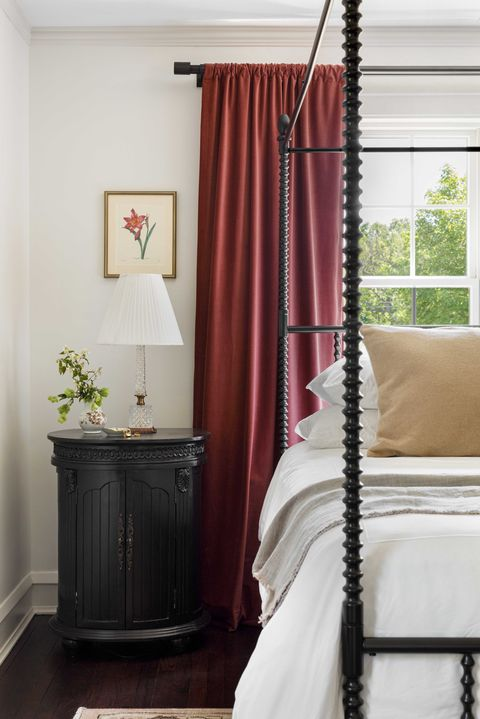 main bedroom, red curtains, white bed with black bedframe and white linen, black side table
