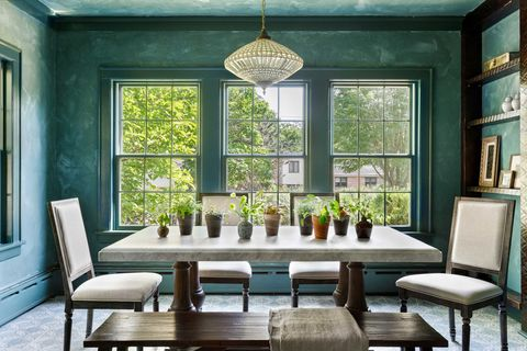 dining room with green walls, dark brown table with white countertop