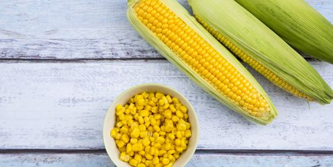 organic corncob on wood, maize in bowl