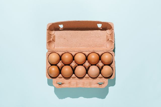 organic eggs in cartons tray on blue background flat lay, top view