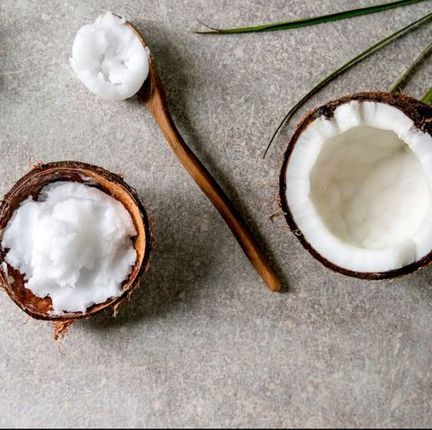 Organic vegan cold pressed coconut oil in coconut shell and wooden spoon over grey texture background. Healthy eating. Flat lay. copy space