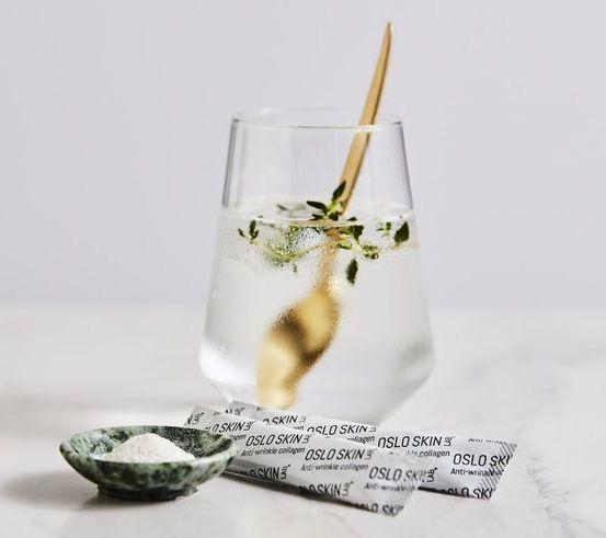 een glas met gouden lepel en de oslo skin lab producten