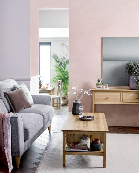 Small living room space with light walls and wooden furniture