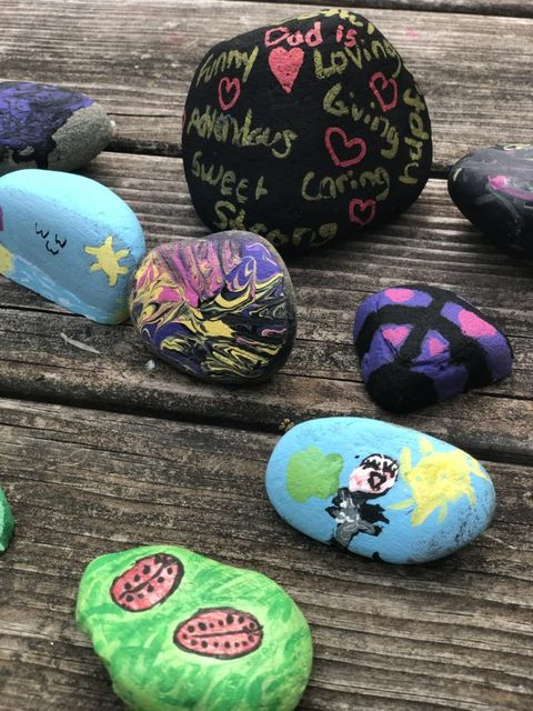 small, smooth hand painted stones with various pictures on them