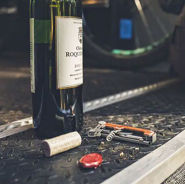 a multi tool with an orange handle and corkscrew next to an open bottle of wine