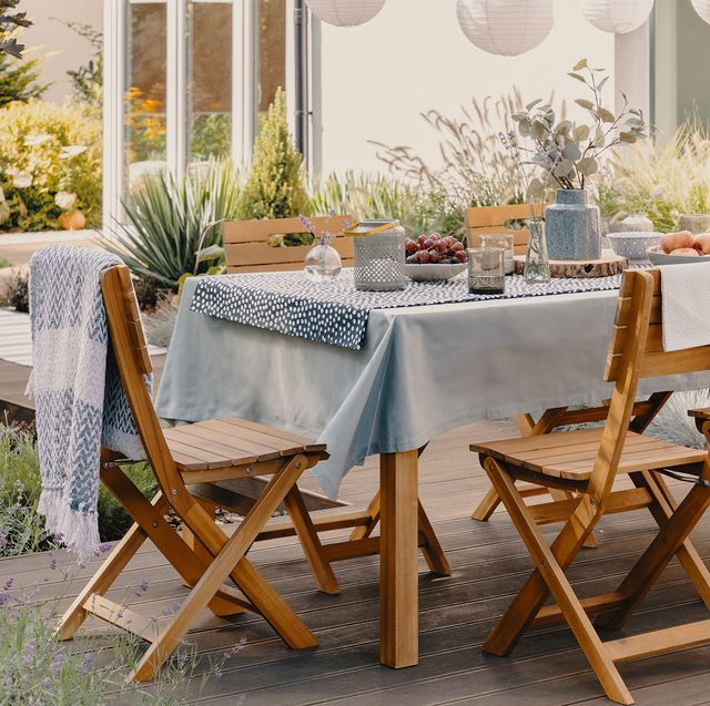 outdoor table and chairs set for a dinner party with paper lanterns