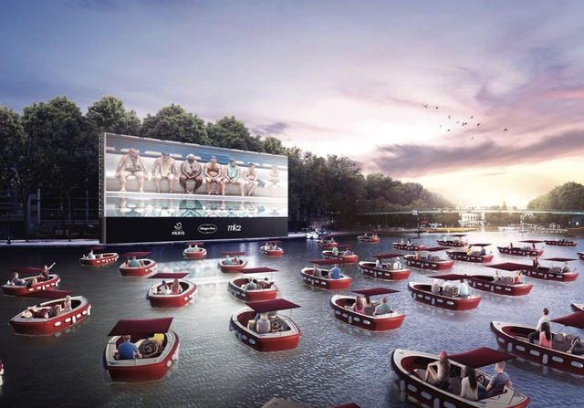 outdoor movie theater on water surrounded by boats