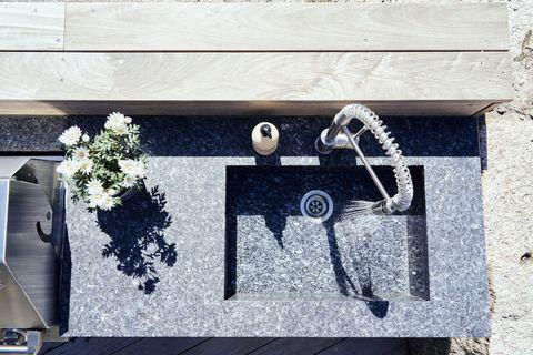 outdoor kitchen, lundhs blue silk sink and worktop surfacee