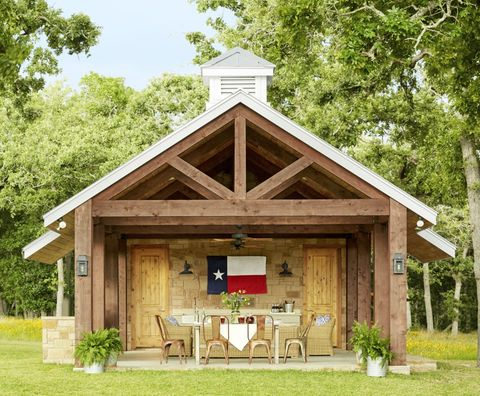 An outdoor wood beam pavilion with a Texas state flag hanging and a set of table and chairs