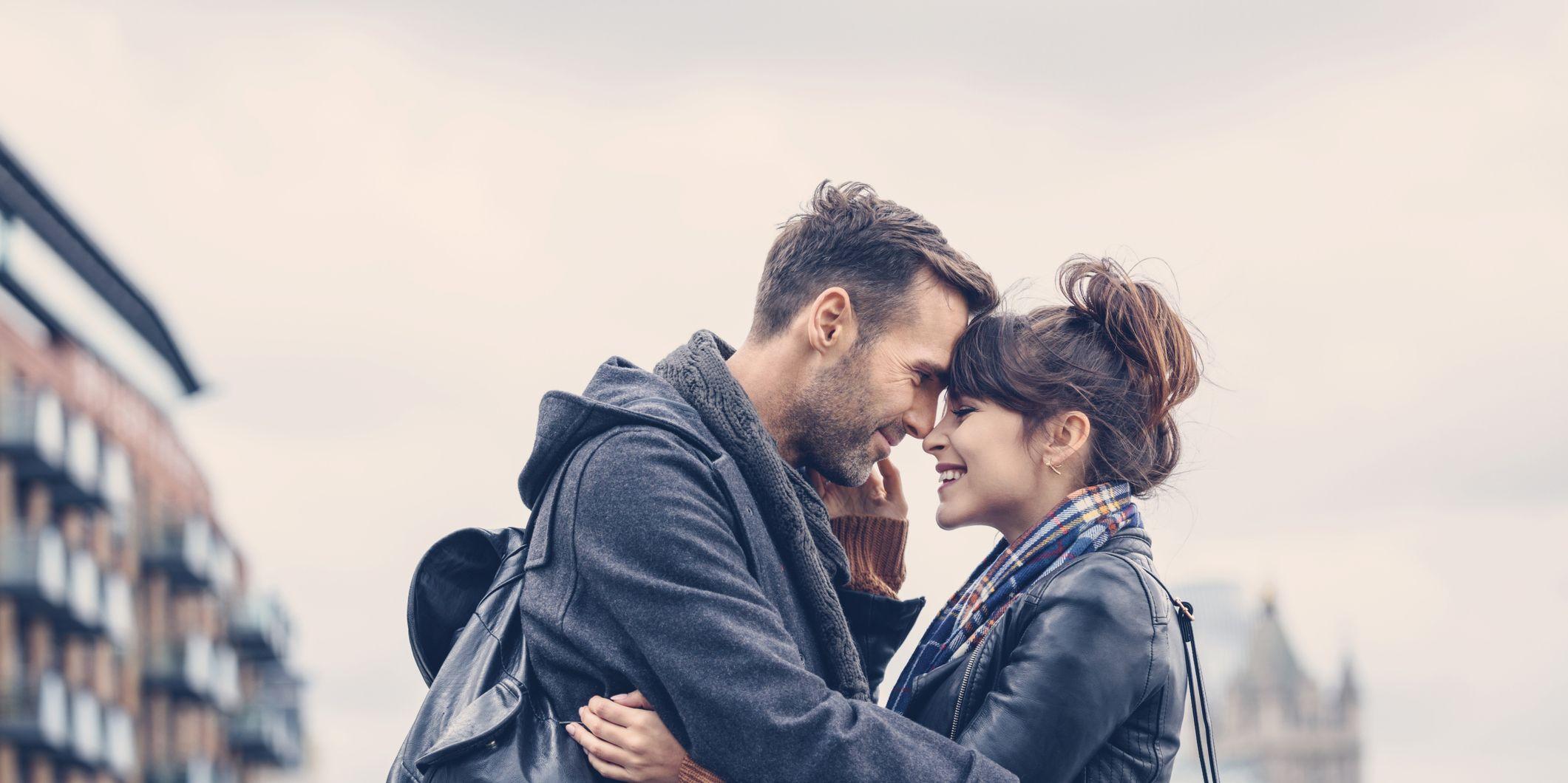 Outdoor shot of happy couple flirting on bridge in London