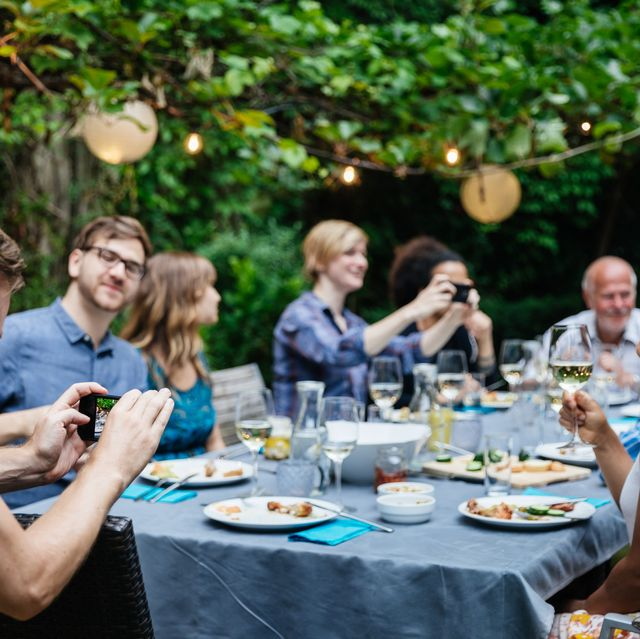 a man taking a photo of his friends drinking and eating at a family barbecue