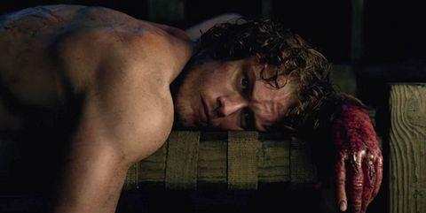 jamie fraser tumbado y con la mano ensangrentada en una escena de outlander