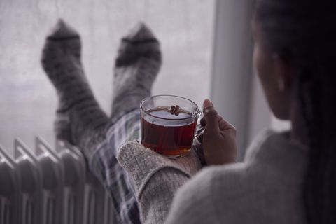over the shoulder image of a woman drinking tea at home in cold and wet weather