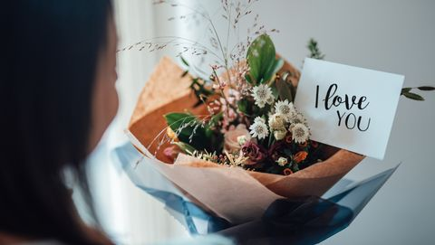 """over the shoulder view of a unrecognisable woman receiving flower bouquet with greeting card written """"i love you"""""""