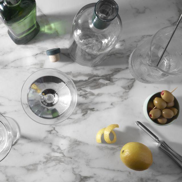 overhead shot of a martini glasses, bottles, lemon, lemon twist, peeler, olives, and cocktail mixing glass on marble