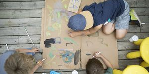Overhead view brothers painting lemonade stand in back yard