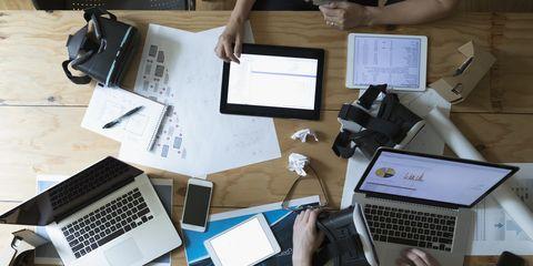 Beeld van designers met VR simulator brillen, terwijl ze aan het werk zijn op tablets en laptops.